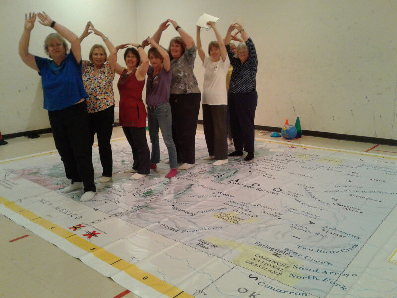 Members of the Colorado League of Women Voters perform the On the Move lesson on the Giant Map of Colorado.